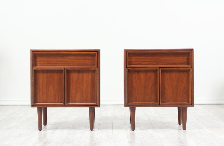 Pair of nightstands designed by John Keal for Brown Saltman in the United States circa 1950's. This spacious pair of nightstands feature a single drawer above an enclosed compartment. The push-open doors and drawer display a beautiful recessed front