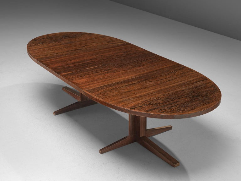 John Mortensen for Heltborg Møbler, dining table model HM55, rosewood, Denmark, 1960s.   Large oval dining table with 2 leafs. This table has a very interesting base. In small position the legs form a cross with four points. When extended the