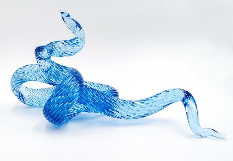 A single rod of translucent and striated marine blue glass is twisted, looped and shaped into an elegant wave by artist John Paul Robinson. The design is enhanced by light that sparkles on the complex surfaces of this table top sized