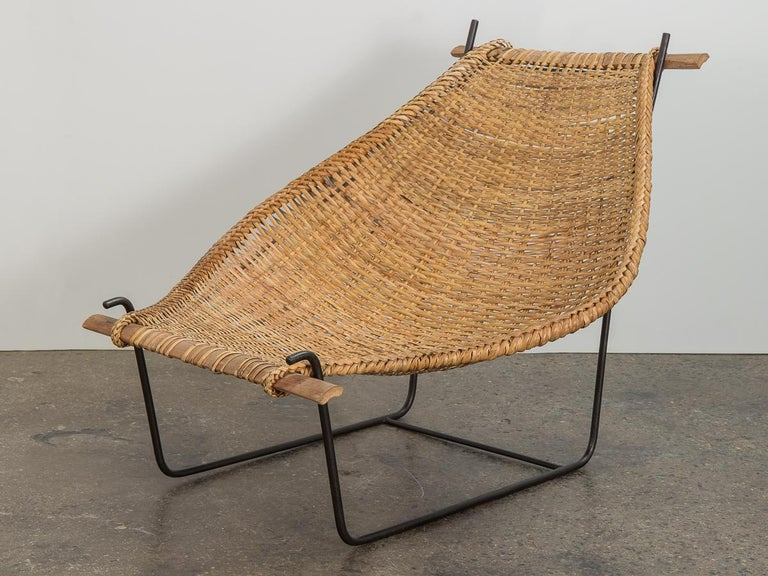 Modernist Duyan lounge chair designed by John Risley. Minimal iron frame supports a curved sling, finished with a beautiful braided edge. Bamboo supports at each end. A delightful mélange of traditional weaving craft and modern design. The chair is