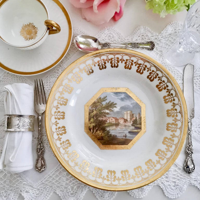 This is a dessert plate made by John Rose / Coalport in circa 1810, which was the late Georgian period. The plate is decorated with a superbly painted named landscape of the West Gate of Canterbury by the famous porcelain painter Thomas Baxter,