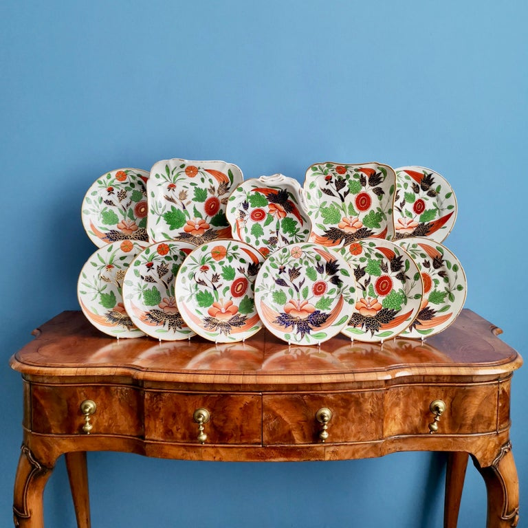 This is a very boldly decorated John Rose / Coalport dessert service made in about 1805, which is known as the Georgian period. The service is decorated in a very bold Imari pattern and consists of eight plates, two square dishes and one shell