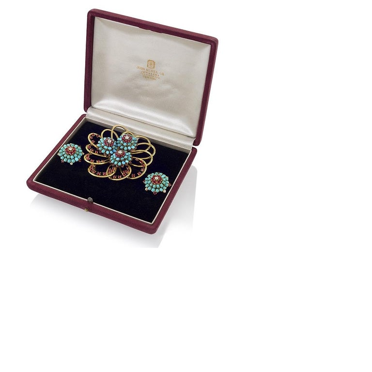 An American mid-20th century 18 karat gold brooch and earrings suite with rubies, diamonds and turquoise by John Rubel. The brooch is an openwork bloom comprised of large gold loops studded with accenting rubies that expertly play with the negative