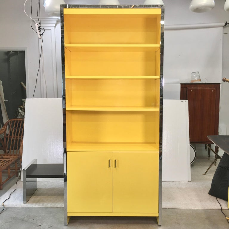 Cheerful and well proportioned tall bookcase cabinet which can also serve as a dry bar. A hefty band of polished chromed steel along three front edges. Three adjustable height shelves above a double door cabinet in which is a single adjustable
