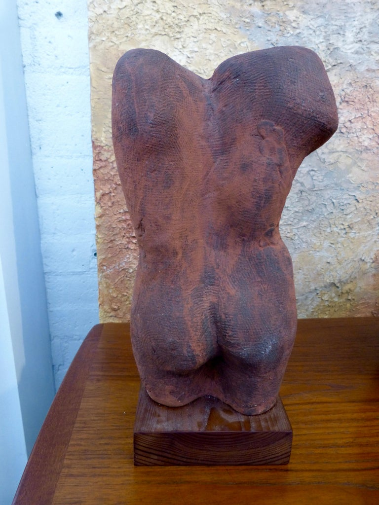 A pottery nude torso out of John Tuska's estate. This pottery torso is unsigned. Minor glaze flakes and imperfections. Some fading to the wood base.
