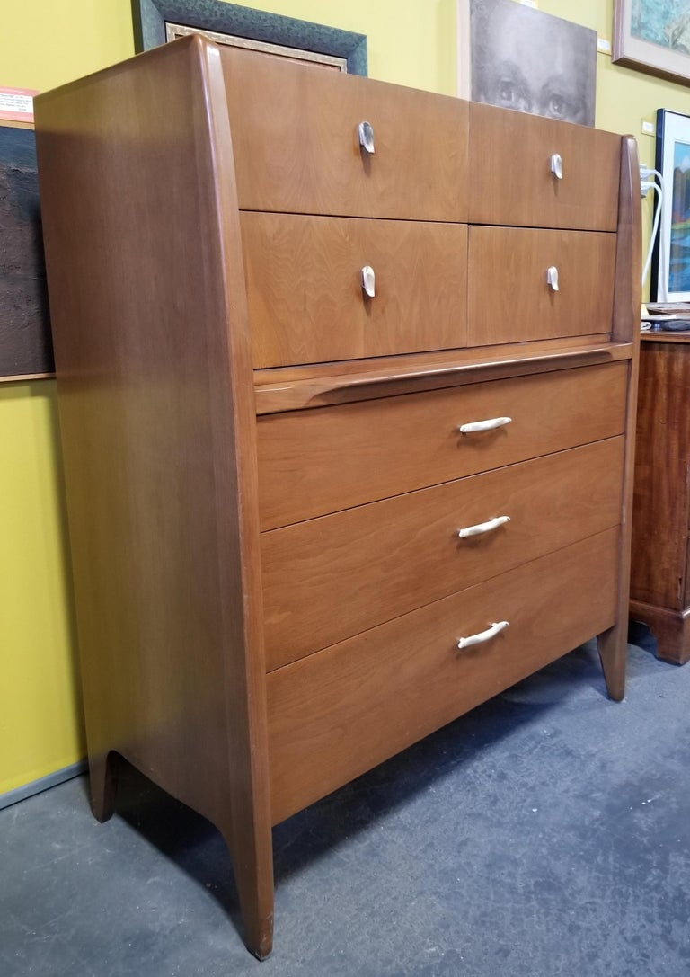 Quality craftsmanship and materials in this Mid-Century Modern highboy dresser designed by John Van Koert for Drexel Furniture. All wood construction solid oak secondary woods and dovetail detail. Drop-down drawer reveals flip up mirror. Very good