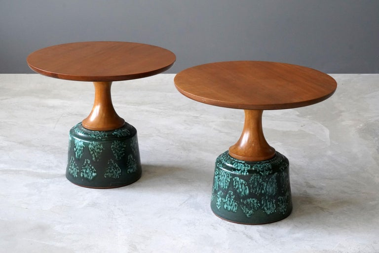 A pair of side table or occasional tables, designed by John Van Koert and produced by Drexel Furniture Company, North Carolina, America.   Finely carved cherrywood tops are mounted atop the glazed ceramic bases.   Other designers of the period