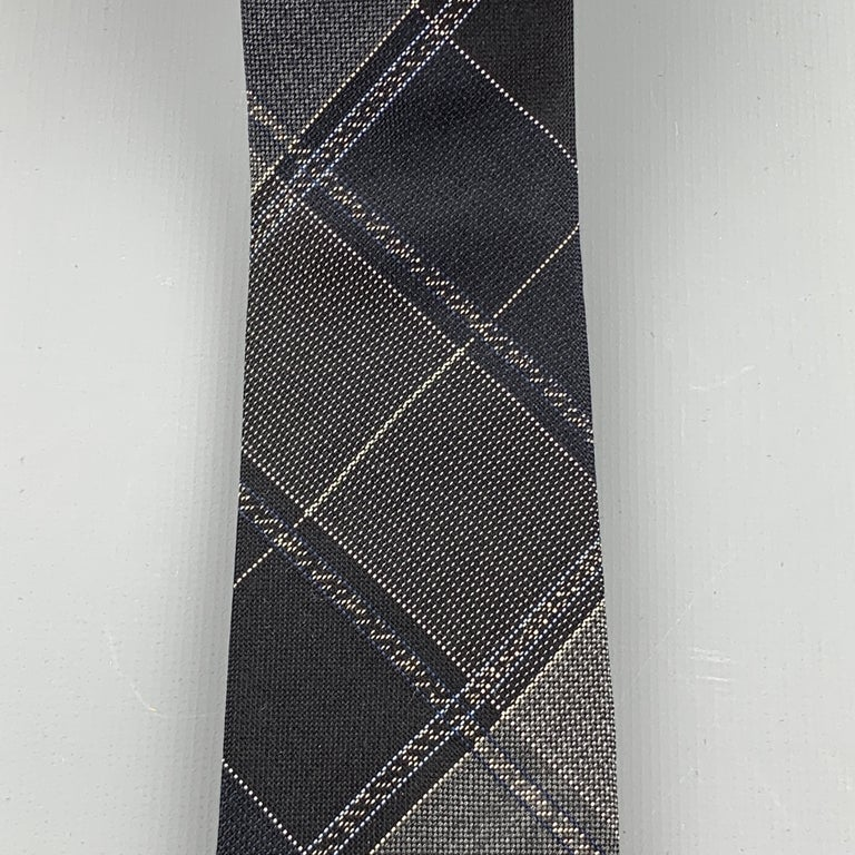 JOHN VARVATOS skinny necktie comes in black silk twill with all over gray plaid print. Made in Italy.  Excellent Pre-Owned Condition.  Width: 2.25 in.