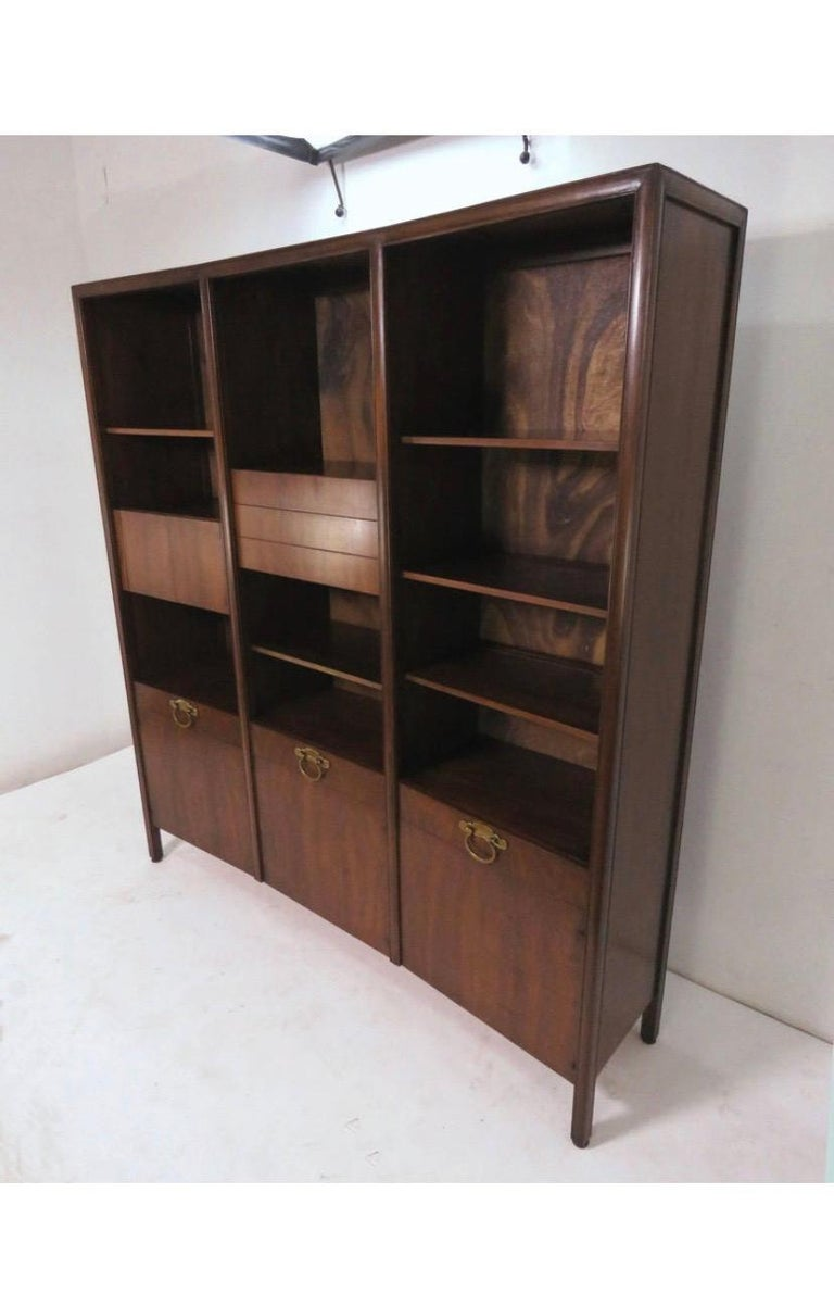 Stunning walnut bow front freestanding wall unit designed by Bert England for John Widdicomb, circa 1950. Features solid brass hardware, upper cabinets and shelves that are height adjustable within their three bays and a finished walnut panel back