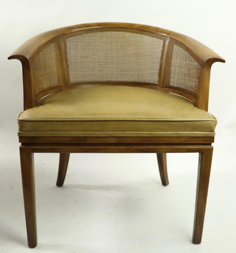 Stylish and chic barrel back lounge chair by John Widdicomb. Solid wood frame, with caned sides and backrest, leather upholstered seat. This chair is in clean, original and ready to use condition. Second chair available but as is. not included in