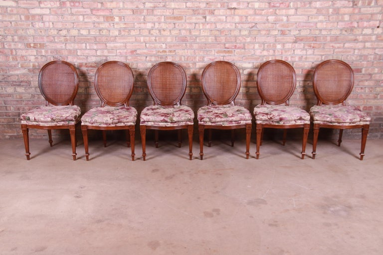 A gorgeous set of six French Regency style dining chairs  By John Widdicomb  USA, circa 1970s  Carved walnut, with floral upholstered seats and caned oval backs.  Measures: 21