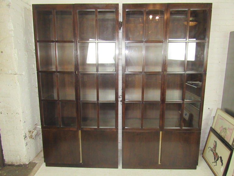 Mid-Century Modern mahogany bookcases with glass front doors and glass shelves. Lighting inside, storage cabinet below. Price is for single unit. (Please confirm item location - NY or NJ - with dealer).