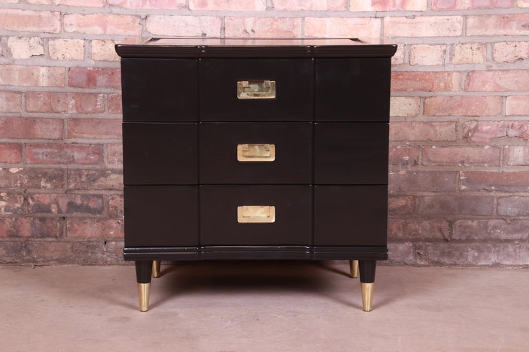 An exceptional Mid-Century Modern Hollywood Regency Campaign three-drawer bedside chest or bachelor chest  By John Widdicomb  USA, 1950s  Black lacquered solid cherry wood, with original brass hardware and brass-capped feet.  Measures: