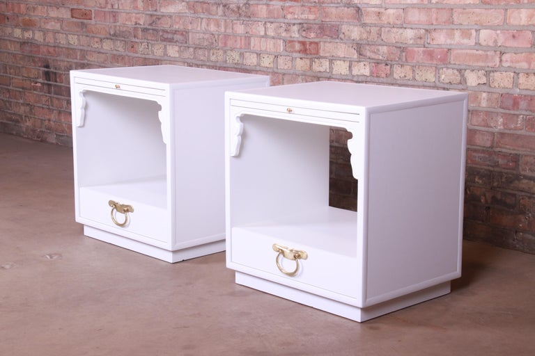 An exceptional pair of Mid-Century Modern Hollywood Regency chinoiserie single-drawer nightstands or end tables  By John Widdicomb  USA, 1950s  White lacquered walnut, with original brass hardware.  Measures: 22