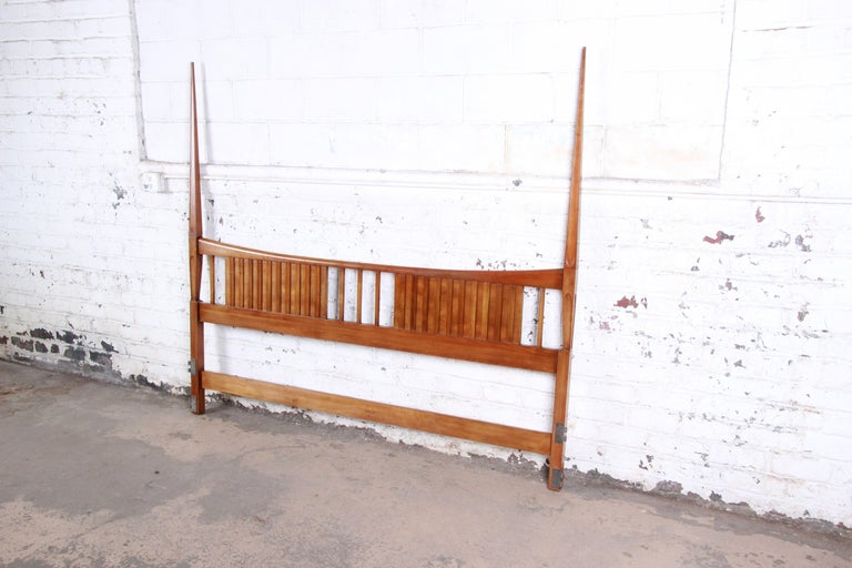 A gorgeous Mid-Century Modern sculpted cherrywood king size headboard by John Widdicomb. The headboard features gorgeous wood grain and sleek mid-century design, with tall tapered posts. The original label is present. The headboard is in excellent