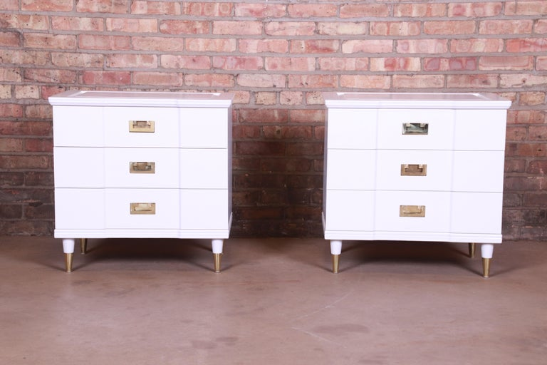An exceptional pair of Mid-Century Modern Hollywood Regency Campaign three-drawer nightstands  By John Widdicomb,  USA, 1950s  White lacquered solid cherrywood, with original brass hardware and brass-capped feet.  Measures: 25
