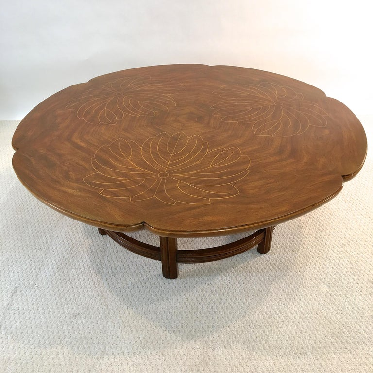 Not commonly seen clover or scalloped edged form John Widdicomb round walnut coffee table with a contrasting wood inlay leaf form design on the top, circa 1960.  Metal label on underside Wm. A. Berkey division of John Widdicomb.  Beautifully