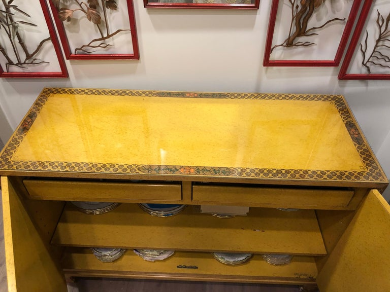 This hand painted chest or server by John Widdicomb has a chinoiserie look. Upon opening it you will see 2 drawers and several shelves in the interior also hand painted on the top and sides having a glass on top.