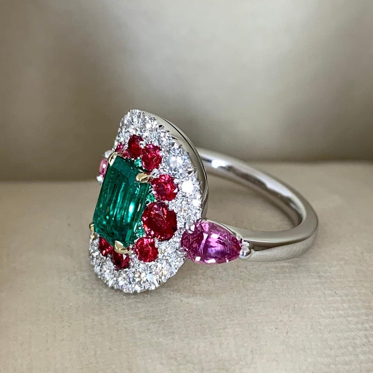 One of a kind ring in 18K White gold 8,9 g. with prongs in yellow gold. Set with an unoiled loupe clean emerald centerstone 1,10 Carat., Unheated poppie ( hot pink) red spinel from Mogok, Burma 0,8 ct., 2 pear shape unheated pink sapphires from
