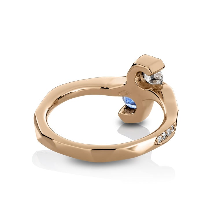 One of a kind ring in 18K Rose gold 4,6 g set with a brilliant-cut Sapphire 0,35 ct., white brilliant-cut diamond 0,23 ct., pave set sapphires 0,062 ct; pave set icy white , white and natural coloured blue diamonds 0,25 ct. One side of the ring is