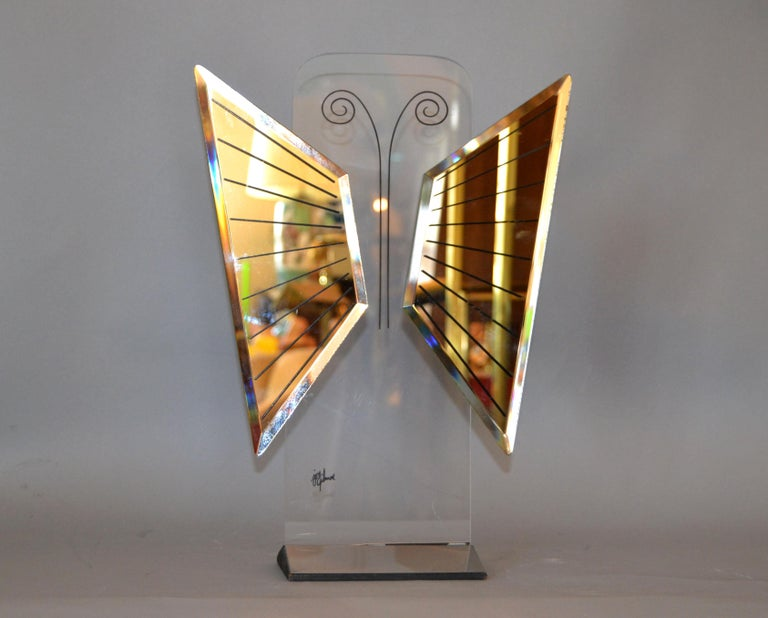 Unique Mid-Century Modern art mirror sculpture in chrome and Lucite shaped in form of a butterfly. Signed by the Artist Jon Gilmore on the Lucite. Beautiful for your vanity or boudoir.
