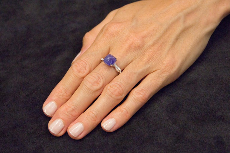 Jona design collection, hand crafted in Italy, 18 karat white gold ring centering a cabochon Tanzanite weighing 6.32 carats. The shoulders are set with 84 White diamonds weighing 0.39 carats in total, F color, VVS1 clarity. Dimensions: 1.18 in. H x