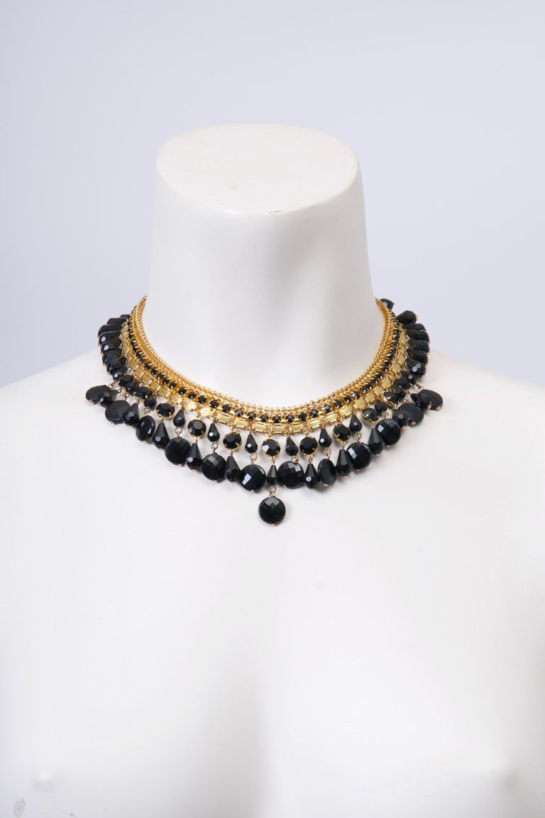 Goldtone and black bead necklace by Jonné, a short-lived division of Schrager, sits gracefully at the nape of the neck. A double row of various faceted black beads are suspended from the goldtone neckpiece, which is composed of three different rows,