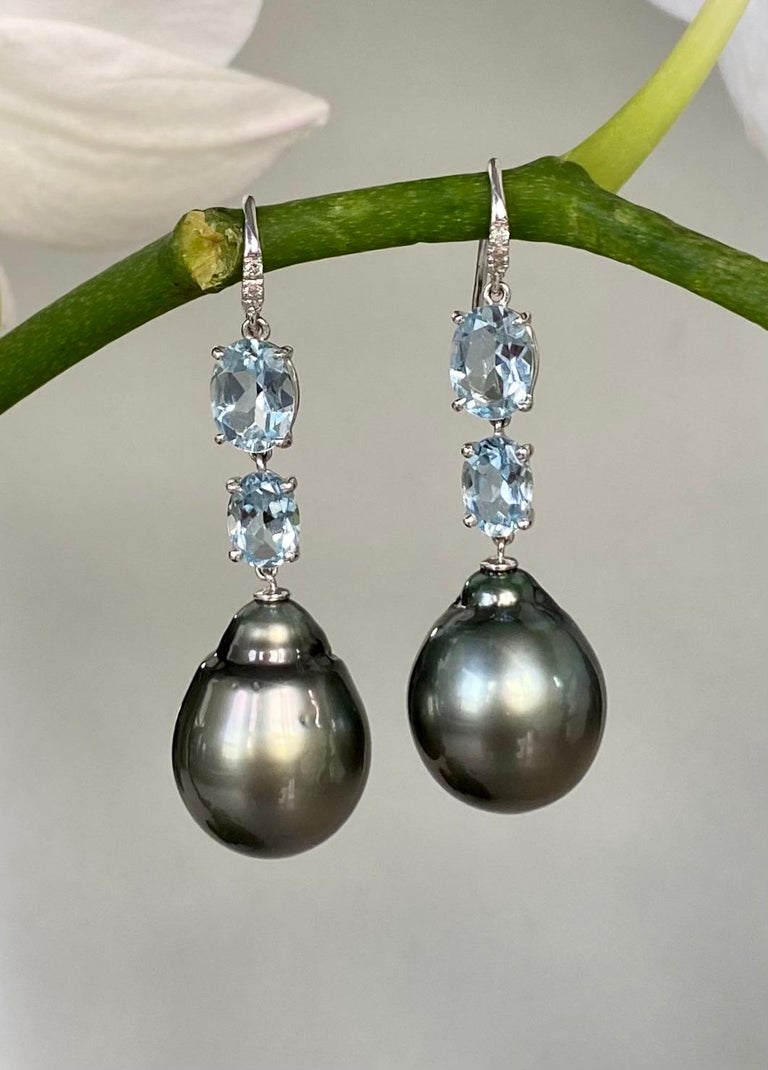Black Tahitian pearls, faceted aquamarines and diamond dangle earrings, handcrafted in 18 karat white gold.  These exquisite one-of-a-kind black Tahitian baroque pearl earrings contrast with oval faceted aquamarines and diamonds to give you a