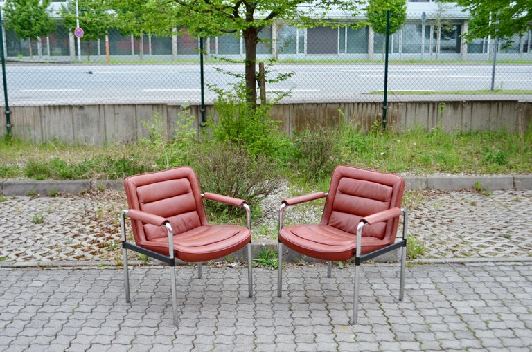 This armchair modell series 8400 was designed by Jorgen Kastholm for Kusch + Co  The pieces comprise matte-chromed tubular steel bases and red leather upholstery along with armrests. The armrests are well patinated Great seating comfort with the