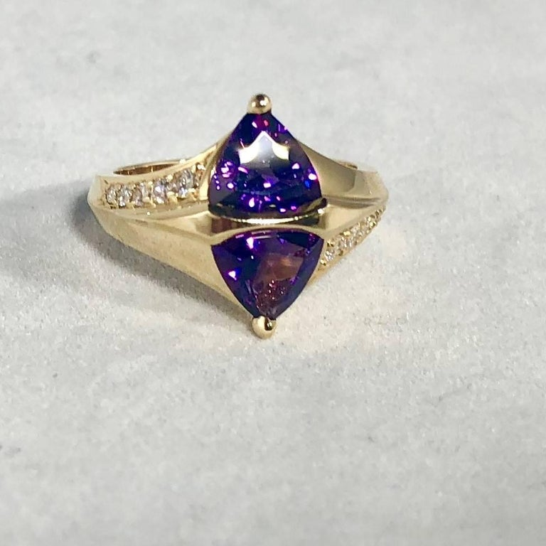 Jose Trillos 18 karat Amethyst and diamond cocktail ring. This piece is created in 18 karat yellow gold weighing 7.1 grams/ 4.6 dwt. The geometric design includes 2 trillion cut Amethyst, each amethyst is 6.5mm in size equaling 2.50 carat total