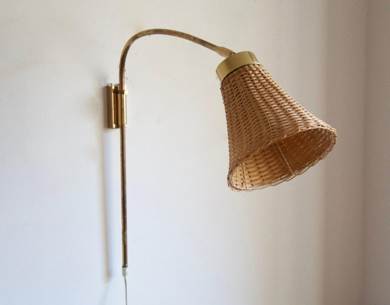 An adjustable wall light / sconce / task light. Designed by Josef Frank 1920s, produced by Svenskt Tenn, Stockholm, Sweden, c. 1950s.   Stated dimensions include lampshade as is illustrated. Assorted vintage rattan lampshade.  Other designers of
