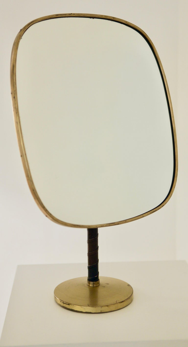 Large and rare table mirror designed by Josef Frank and manufactured by Nordiska Kompaniet in Stockholm. Adjustable in height and ankle. Mirror size: 40cm high/ 37cm wide – 15.35 inch / 14.17 inch. Height from 49cm to 65cm adjustable – 19.29 inch