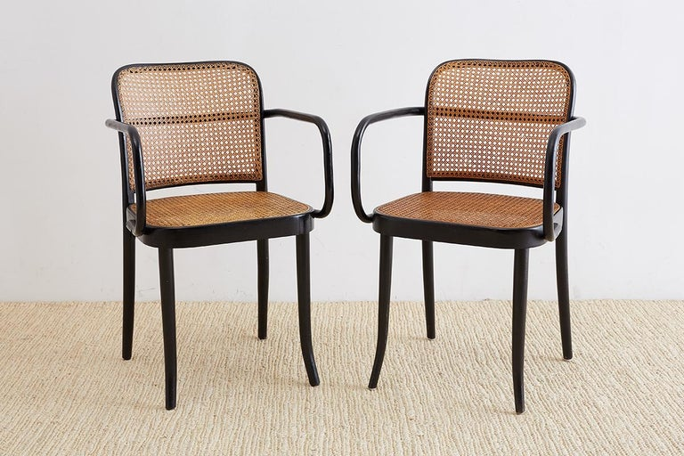 Pair of black 811 bentwood and cane Prague armchairs designed by Josef Hoffman for Stendig after Thonet. Sleek design from 1925 constructed from beechwood frames with hand-caned inserts. Imported by Stendig for Thonet. These chairs have a rare black