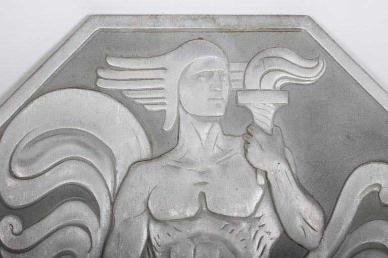 Cast in aluminum, this rare relief panel depicts a kneeling nude male figure with a torch whose flame echoes the billowing folds of his drapery. The figure is wearing a helmet in the Greek manner, and is looking far afield, perhaps representing