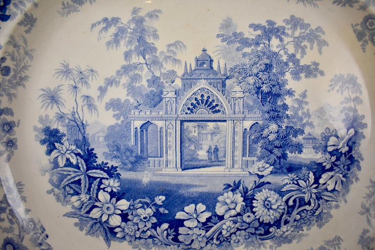 From the pottery works of Joseph Heath & Co. Tunstall, Staffordshire, England, an earthenware, underglaze tissue printed platter, in the 'Persian' pattern, circa 1828 – 1841. 19th Century A romantic Architectural theme with a floral and scroll