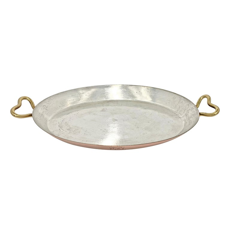 An early 20th century copper au gratin pan with bronze handles and an engraved monogram (