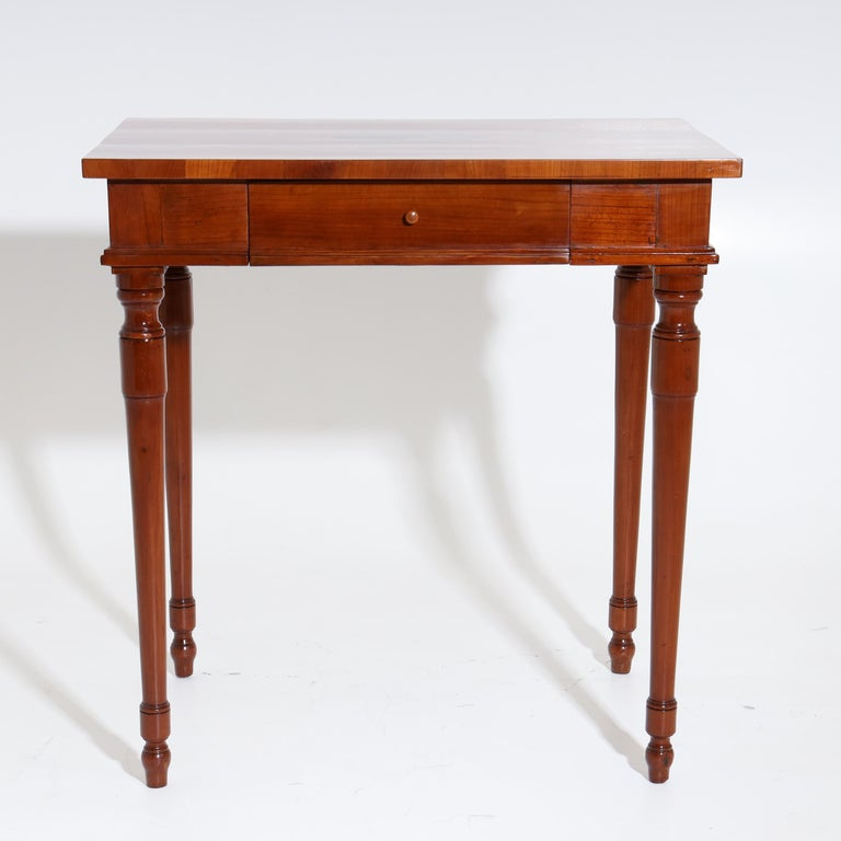 Side table made of cherry, standing on conical and balustered pointed legs, with straight frame and one drawer. The slightly protruding tabletop is decorated with a medallion-shaped inlay with putto and bird.