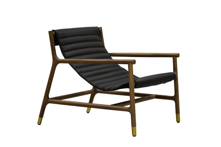 Contemporary style Joyce low armchair made of ashwood with leather tufted seat and brass tips. Designed by Libero Rutilo