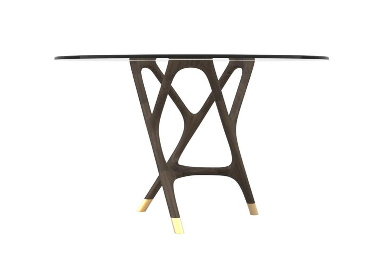 Contemporary style Joyce round dining table made of turned ashwood with glass top and brass tips. Designed by Libero Rutilo