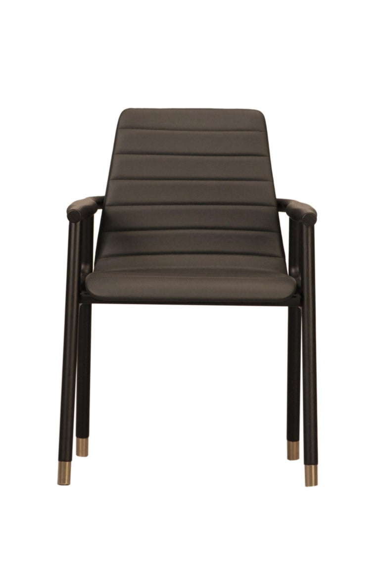 Contemporary style Joyce dining armchair made of ashwood with leather tufted seat and brass tips. Design Libero Rutilo