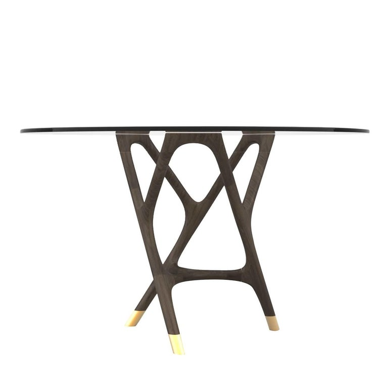 This round dining table features an wengé ash wood structure with a glass top and brass details. Part of the Joyce collection, it represents a blend of past and present, innovation and tradition in the attempt to shape objects designed to last over