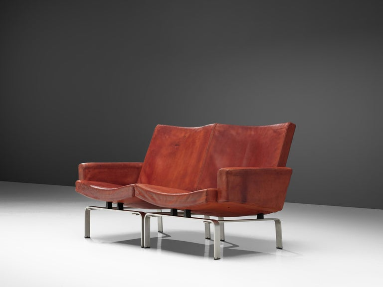Jorgen Hoj for Niels Vitsoøe, settee, leather and aluminum, Denmark, 1963.  Exclusive cognac leather sofa designed by Jorgen Hoj who worked in the same atelier together with Poul Kjaerholm. The Sofa '202' manufactured by Niels Vitsoøe is supported