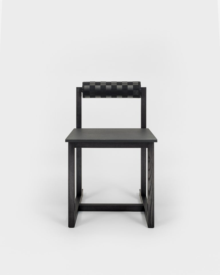 The chair's framework conjures the minimalist simplicity of Donald Judd's Library Chairs. Available in either natural or ebonized Eastern Ash with black on black checkerboard backrests. Punx not dead.