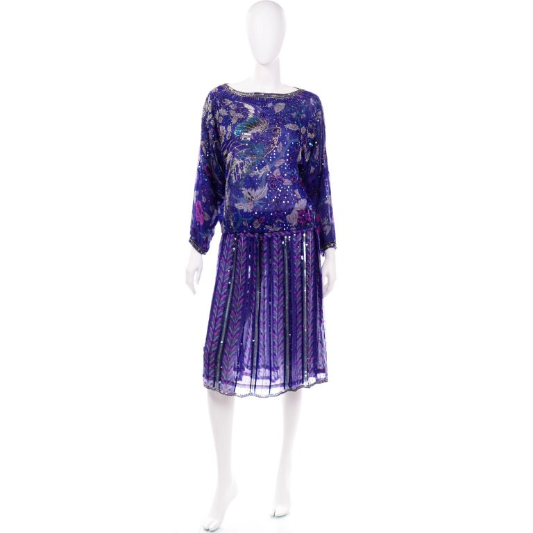 This is a stunning beaded and sequin 2 piece dress from Judith Ann Creations. The outfit includes a gorgeous silk lined long sleeve blouse with a beautiful bird motif. and a silk lined skirt. The top has a wide boat neck that is fully beaded and has