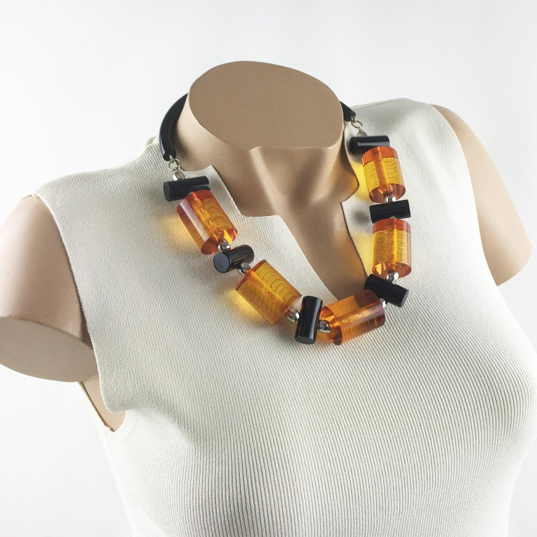 A fabulous piece of jewelry-art by Judith Hendler. This necklace is from the 1980s. It has the iconic acrylic - Lucite neck tube ring and from it are elegant geometric large beads acri-gems in assorted colors of transparent orange and true licorice