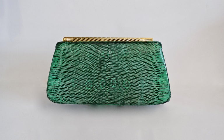 Elevate your bag collection with this amazing Judith Leiber clutch! Circa 1980s, this bag is crafted from green and black snake skin and features gold hardware, a chain shoulder strap and a lever to open the peg closure. Both front and back face