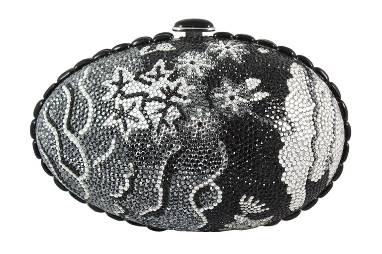 Judith Leiber clutch  Black, grey, and silver rhinestones in a floral design  Black and silver snap closure  Black trim around the egg  Silver chain strap that can be stored inside  Soft silver leather lining Comes with silver coin purse, mirror,
