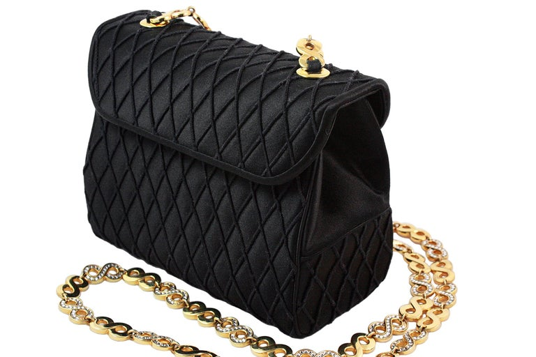 Judith Leiber crossbody bag  Black satin with diamond thread pattern  Hidden gold snap closure  Gold rhinestone infinity chain strap  Black satin lining Inner card slot and zippered pocket Comes with black coin purse, gold mirror and blue dust-bag