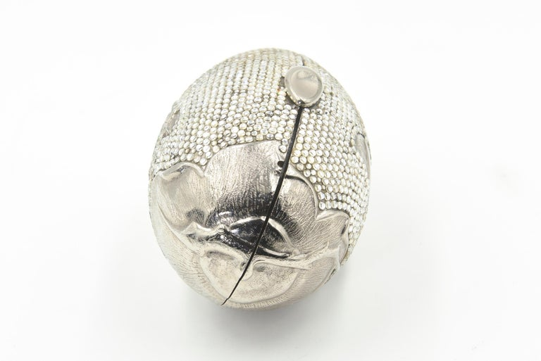 Judith Leiber Minaudières are a useful piece of art.   This purse is silver toned metal oval box clutch from Judith Leiber Vintage features a floral design that includes a flower, leaves, ladybugs, a spider an a fly.  It has a thin silver chain