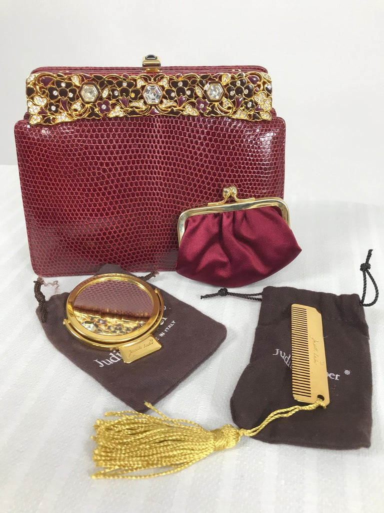 Judith Leiber jewel clasp, burgundy lizard clutch or shoulder bag with accessories, comb, mirror and change purse including protector bags and box. The bag is in beautiful condition, barely used. The frame is gold metal with shades of burgundy